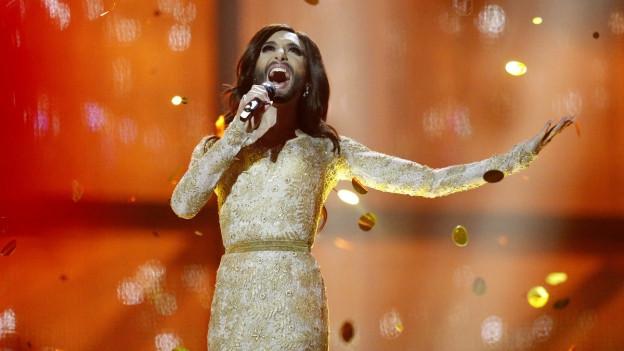 Conchita Wurst cun vestgì d'aur, chavels lungs e barba sin il palc dal ESC.