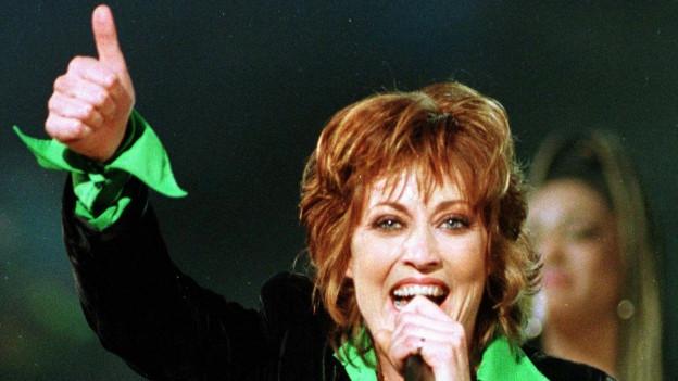 Katrina Leskanavich chanta cun il microfon enta maun.