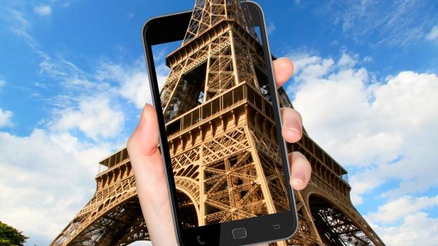 In telefonin che fotografescha la tur Eifel a Paris.
