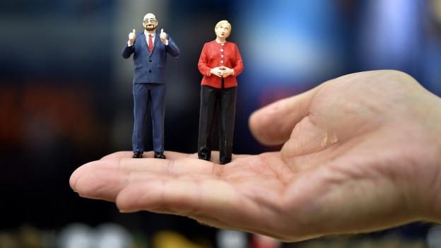 Figuras da Merkel e Schulz sin in maun.