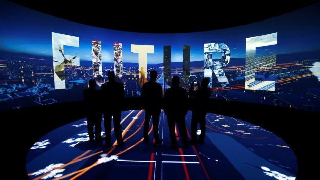 Visitaders persequiteschan ina preschentaziun da 3D da «Neom».