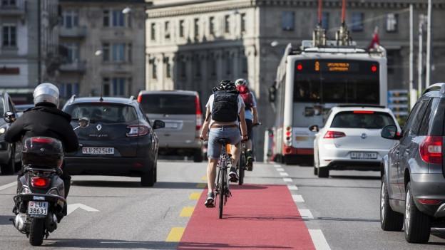 velocipedists sin ina via da velos permez il traffic (autos, bus e vespa) en ina citad