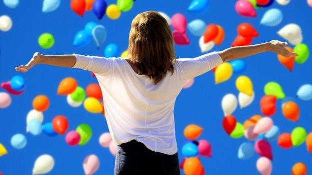 Fotografia d'ina dunna ventiraivla che mira en in tschiel blau plain ballons colurads..