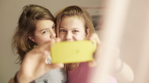 Duas mattas che fan selfies cun in smartphone.