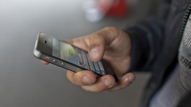 Ina persuna cun in smartphone.