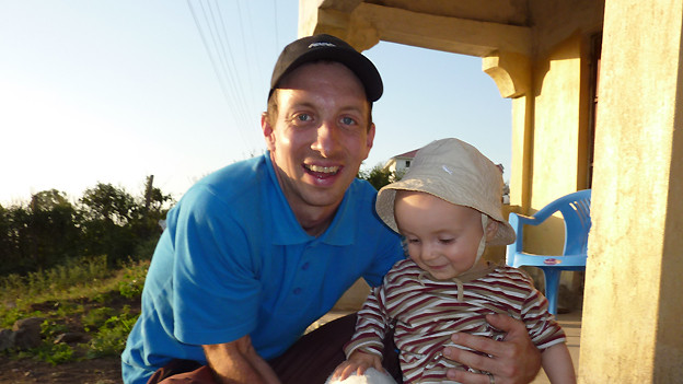 Andres Wirz mit seinem Sohn Nils (15 Monate) vor dem Haus eines Nachbarn in Abura.