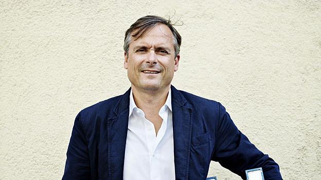 Axel Hacke vor Wand mit weiss-beigem Verputz.