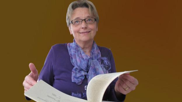 Margrith Ladner-Frei blättert im Prättigauer Mundart-Wörterbuch