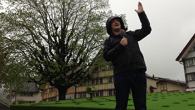 Michael Brunner im Regen auf dem ehemaligen Landsgemeindeplatz Hundwil.