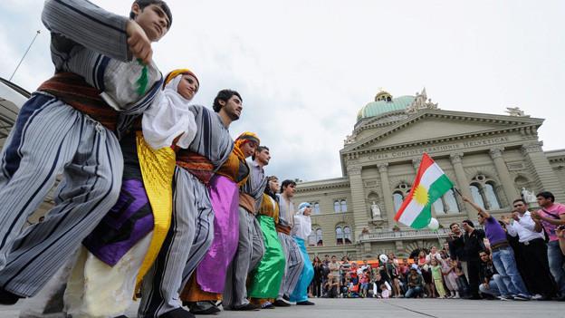 Internationaler Flüchtlingstag 2009: Hunderte Menschen verfolgen eine Tanzperformance des Kurdischen Kulturvereins auf dem Bundesplatz in Bern.