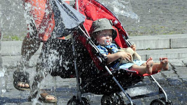 Eine rasante Fahrt mit dem Kinderwagen durch das kühle Nass bringt dem kleinen Liam auf dem Fischmarktplatz in Rapperswil (SG) die gewünschte Erfrischung.