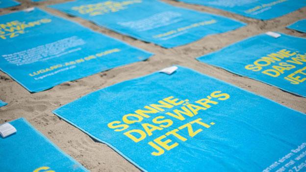 Diese Badetücher ersetzen die Eintrittskarte in drei Strandbäder in Lugano.