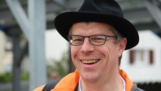 Markus Gasser mit Hut, Brille, oranger Jacke und einem breiten Lachen im Gesicht.