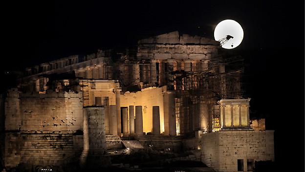 Der Vollmond erstrahlt in perfekter Rundung über der Akropolis in Athen.