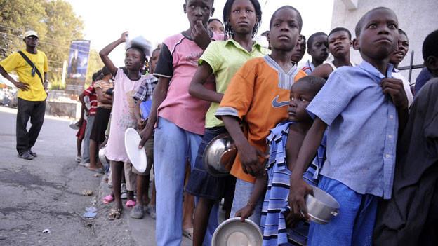 Unverschuldet in einer Notlage: Haitianische Kinder stehen nach dem Erdbeben im Januar 2010 für Reis an.