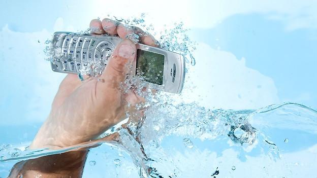 Eine Hand fischt ein Mobiltelefon aus dem Wasser.