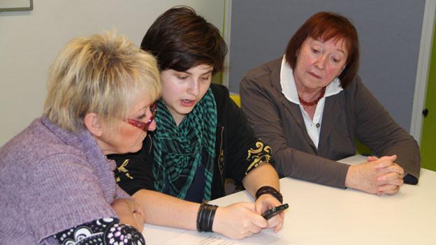 Jugendliche zeigen Seniorinnen und Senioren, wie man Apps auf einem Tablet-Computer anwendet.