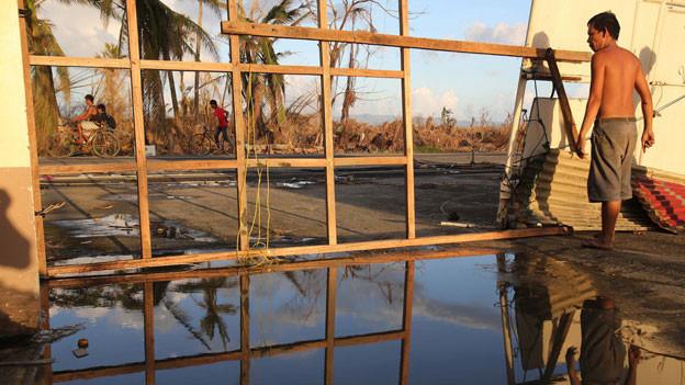 Ein Bewohner in Taclaban vor den Trümmern seines Hauses.