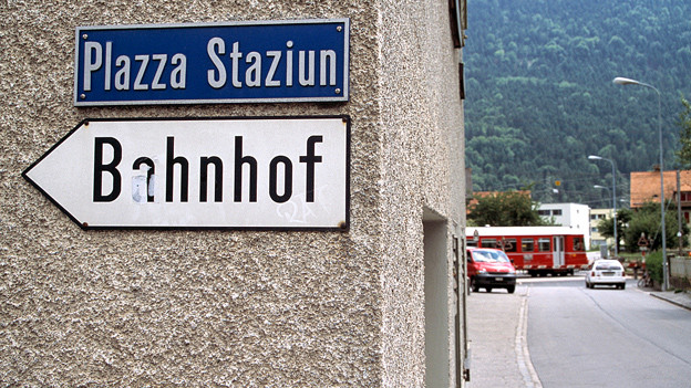 Eine Strasse, zwei Sprachen: Rätoromanische und deutsche Beschriftung in einem engadiner Dorf.