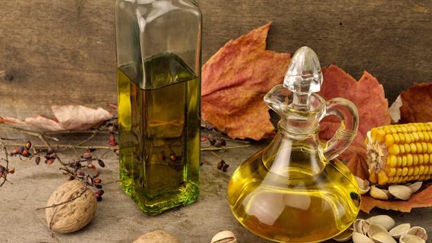 Eine Glasflasche und eine Glaskaraffe mit verschiedenen Ölsorten.