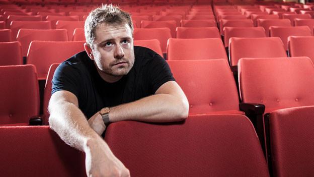 Gabriel Vetter sitzt im roten, leeren Theatersaal