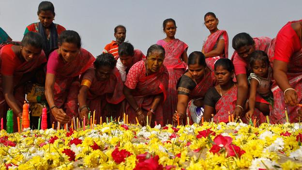 Frauen legen Kerzen und Blumen nieer an einer Tsunami-Gedenkfeier in Chenai (Dezember 2013).