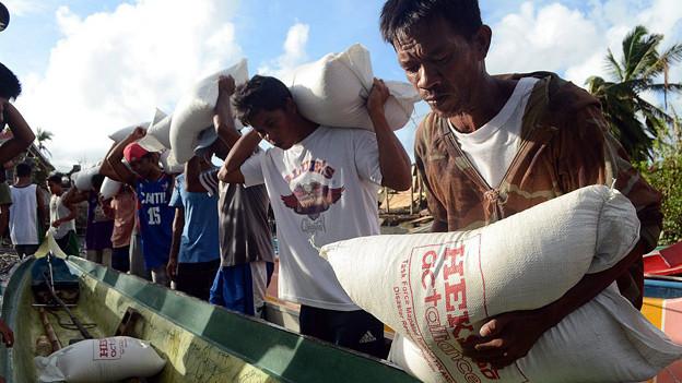 Philippinische Taifun-Opfer nehmen Reissäcke von einem Hilfswerk in Empfang (Insel Panay November 2013).