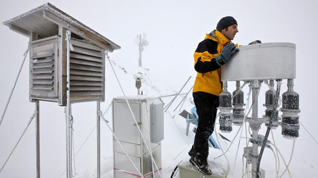 Ein Mitarbeiter des Eidgenössischen Instituts für Schnee- und Lawinenforschung prüft seine Messanlage.
