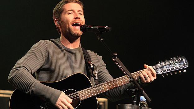 Josh Turner mit Gitarre am Mikrofon.