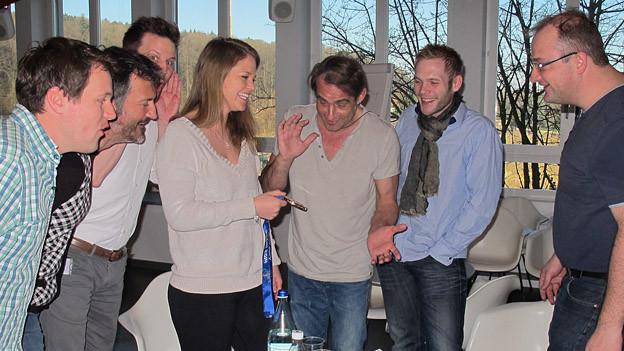 Moderatoren und Redaktoren bestaunen die Bronze-Medaille von Florence Schelling.