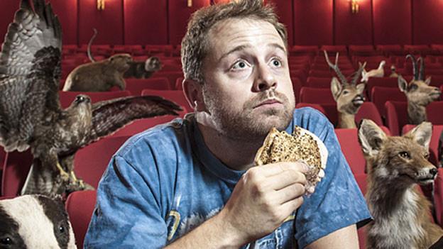 Gabriel Vetter sitzt im Theatersaal und beisst in einen Hamburger