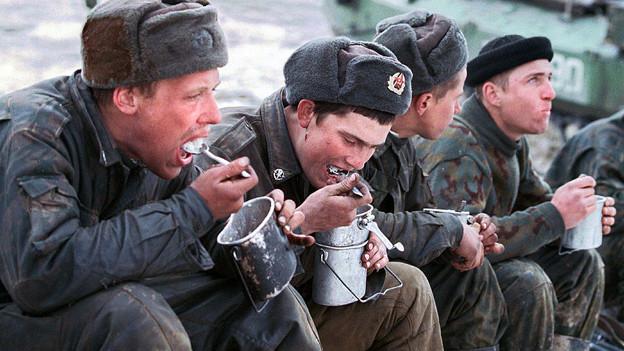 Russische Soldaten essen aus der Gamelle.