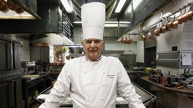 Meisterkoch Paul Bocuse posiert in seiner Küche.