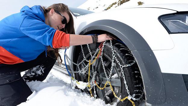 Eine Autofahrerin montiert Schneeketten an den Rädern ihres Autos.