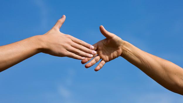 Zwei Menschen reichen sich die Hand.