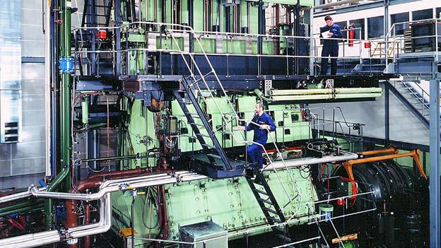 Mechaniker arbeiten an einem Schiffsmotor.