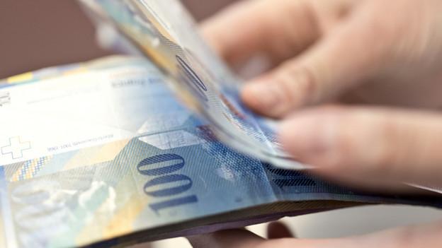Eine Hand hält einen Bund 100-Franken-Noten.