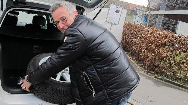 Dani Fohrler nimmt ein Reserverad aus dem Kofferraum