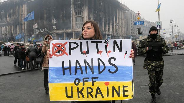 «Putin, Hände weg von der Ukraine» – eine Frau mit einem Plakat im Zentrum Kiews.