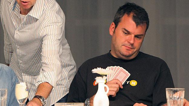 Mike Müller mit Jasskarten in der Hand