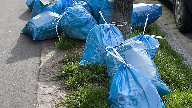 Blaue Müllsäcke auf der Strasse.