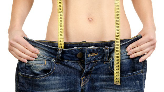 Frau hält sich zu grosse Hose vor den Körper.