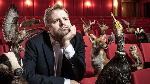 Gabriel Vetter sitzt in einem roten Theatersaal, umgeben von ausgestopften Tieren aller Art
