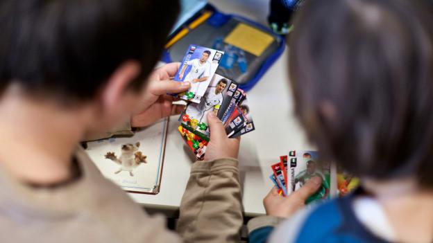 Kinder begutachten und tauschen Panini-Bildchen.