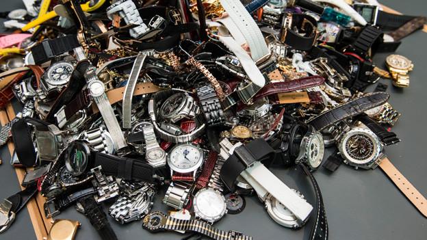 Beschlagnahmte gefälschte Uhren auf einem Haufen.