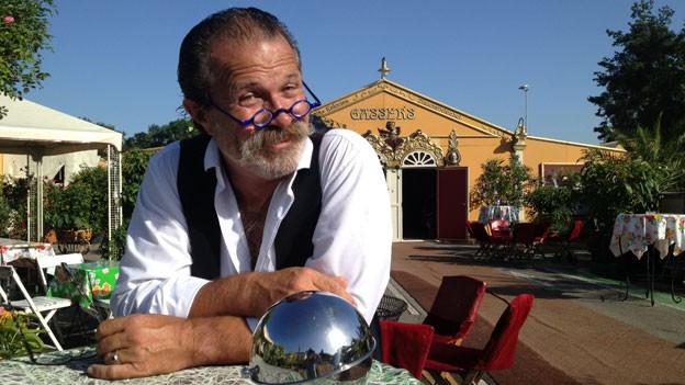 Frithjof Gasser sitzt am Tisch.