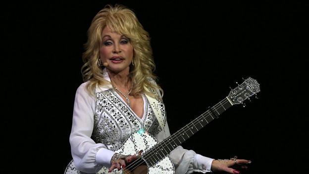 Dolly Parton mit Gitarre und Glitzer-Kostüm.