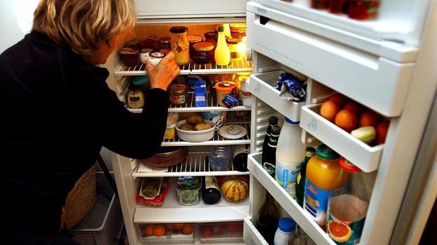 Frau schaut in vollen Kühlschrank.