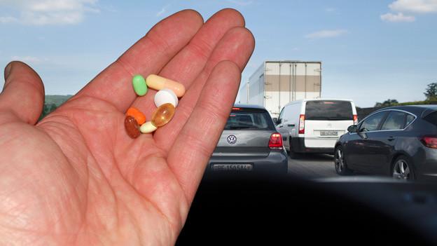 Medikamente in der Hand vor Windschutzscheibe im Verkehrsstau