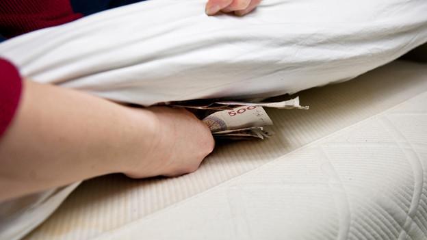 Jemand legt Geld unter die Matratze.